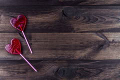 Two heart shaped lollipops on wooden background Royalty Free Stock Photos