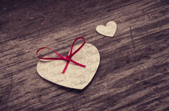Two heart shaped paper Christmas ornaments on rustic wood Stock Photo