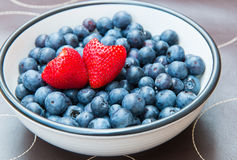 Two heart shaped strawberries in bowl with blueberries. Royalty Free Stock Photo