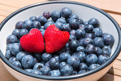 Two heart shaped strawberries in bowl with blueberries. Royalty Free Stock Image
