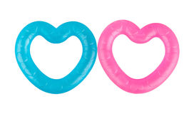 Two heart-shaped teethers. Two heart-shaped teethers blue and pink colors isolated on white background Royalty Free Stock Image