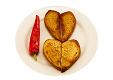 Two heart-shaped toast and spicy red pepper. White plate with two heart-shaped toast and spicy red pepper Stock Photography