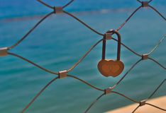 Yellow love lock on bridge. Two heart-shaped yellow love lock hanging on a bridge railing in front of the blue sea in sunlight stock images