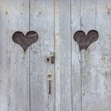 Two heart shapes on antique wooden door stock image