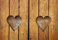Two heart shapes carved in vintage wood close up Stock Photo