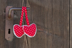 Two heart shapes hanging on an old door handle with polka dots o Stock Images