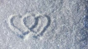 Two heart symbols on the snow, lot of snowflakes flying on the wind. Romantic sign silhouette on winter ground. Valentines day natural background stock footage