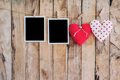 Two heart and two photo frame hanging on clothesline rope with w Royalty Free Stock Images