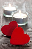 Two hearts. Two red hearts with burning candles stock images