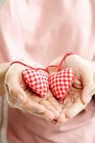 Two hearts. A woman showing two hearts ornaments, can be used for valentine concept royalty free stock images