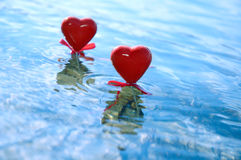 Two Hearts. Two red hearts in blue water conceptual still life stock images