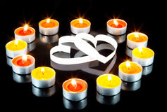 Two hearts. Surrounded small candles light Stock Image