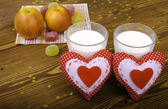 Two hearts, apples on a napkin and two glasses of milk. Royalty Free Stock Images