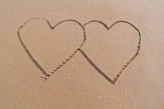Two hearts on the beach. And sand royalty free stock photos