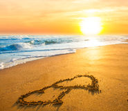Two hearts on beach sand stock images