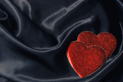 Two hearts on black silk Royalty Free Stock Image