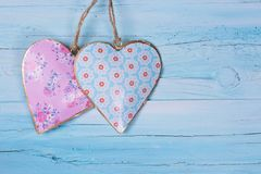 Two hearts. On a blue wooden background royalty free stock image