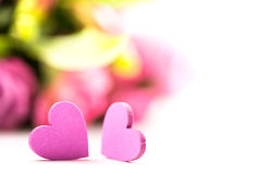 Two hearts with a blurred bouquet of flowers in the background Stock Photos