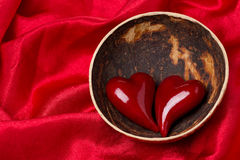 Two hearts in a bowl of coconut on red satin background Stock Image