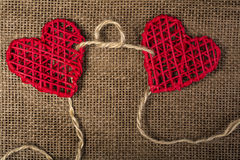 Two Hearts on burlap Background. Wedding Love Concept. Two Hearts linked by rope on burlap Background. Wedding Love Concept Royalty Free Stock Photography