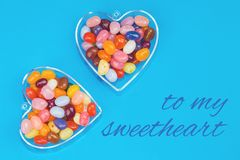 Two hearts with candies on blue background. With card message to my sweetheart. Love and St Valentines day concept flat lay stock photography
