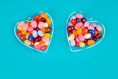Two hearts with candies on blue background. Two hearts with colorful candies on blue background flat lay with copy space. Love and St Valentines day concept stock photo