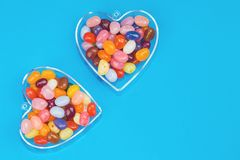 Two hearts with candies on blue background. Two hearts with colorful candies on blue background flat lay with copy space. Love and St Valentines day concept royalty free stock photos