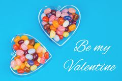 Two hearts with candies on blue background. With Be my Valentine message card. Love and St Valentines day concept flat lay stock image