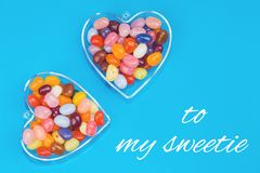 Two hearts with candies on blue background. With card message to my sweetie. Love and St Valentines day concept royalty free stock image