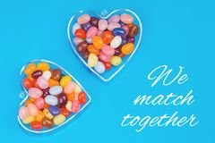 Two hearts with candies on blue background. With We match together message. Love and St Valentines day concept royalty free stock photos