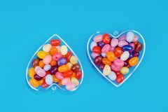 Two hearts with candies on blue background. Two hearts with colorful candies on blue background flat lay with copy space. Love and St Valentines day concept royalty free stock image