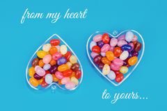 Two hearts with candies on blue background. Two hearts with colorful candies on blue background flat lay with copy space. Love and St Valentines day concept stock images