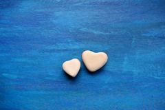 Two hearts candy jelly beans valentine`s blue backg. Two hearts candy jelly beans valentine blue top view background stock photo