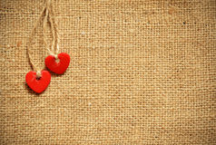 Two hearts on canvas. Two red plastic hearts on canvas background Stock Images