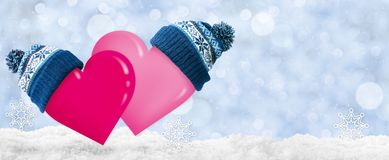 Two hearts in caps with pompoms for Valentine`s Day. Snow and blue background stock photo