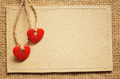 Two hearts on a cardboard. Two red plastic hearts and carton card on a canvas background stock photos