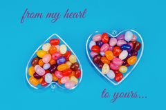 Two hearts with candies on blue background. Two hearts with colorful candies on blue background flat lay with copy space. Love and St Valentines day concept royalty free stock photo