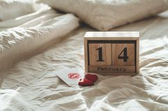 Two hearts cookies, a note with a kiss with wooden calendar 14 February on a white bed. Valentines day concept royalty free stock image
