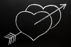 Two hearts with Cupid's arrow hitting through Royalty Free Stock Photos