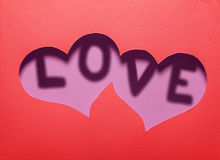 Two hearts cutout in red paper with word Stock Photo