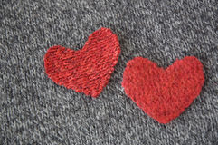 Two hearts on dark fabric Stock Photos