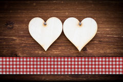 Two hearts on dark sun burned wooden planks. With checked ribbon Stock Images
