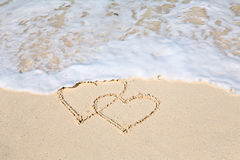 Two hearts drawn on the beach sand, the waives wiping the hearts. Out Stock Photos