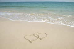 Two hearts drawn in beach royalty free stock photo