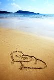 Two hearts drawn in the sand Stock Images