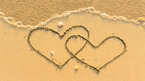 Two hearts drawn on the sand beach with the soft wave Royalty Free Stock Photo