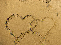 Two hearts drawn on sand of a beach. Royalty Free Stock Images