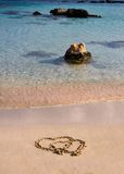 Two hearts drawn in the sand on a beautiful beach Stock Images