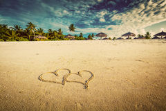 Two hearts drawn on sand of a tropical beach. Vintage royalty free stock images