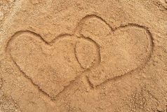 Two hearts drawn in the sand Stock Photos